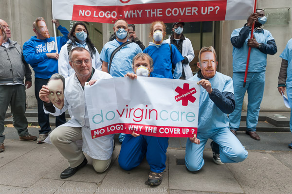 Protesters pose outside Virgin Care HQ in London with a banner 'do Virgin Care' calling for an end to private companies using the NHS logo and for Virgin to stop avoiding tax.